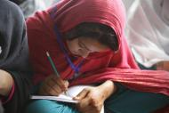 Diwan, 17, practices writing numbers in numeracy class