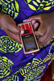 Participant in Rwanda demonstrates using mobile money. Photo credit: Alison Wright