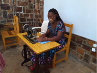 Jeanette, a graduate of Women for Women International, wears a mask while sitting at her sewing machine to create more masks