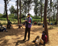 One man stands in a circle of other men, attending the Men's Engagement Program in Rwanda. They are all wearing masks created by women graduates of the signature program at the Women's Opportunity Center