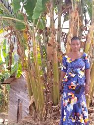 Elizabeth, a participant of Women for Women International - DRC, stands in front of trees in a patterned blue dress