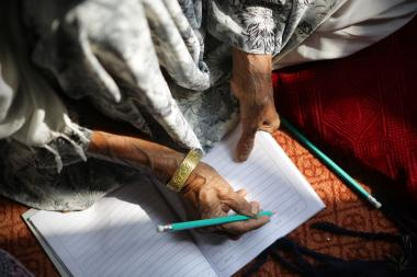 A woman, 60, practices numeracy in class