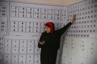 Instructor in front of numbers on a wall