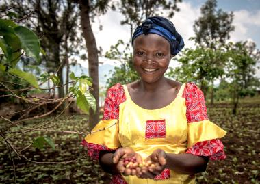 Women holding coffee beans smiling