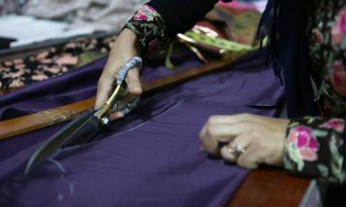 Womans hand cutting cloth with scissors