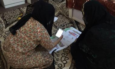 Woman sitting on floor looking at her workbook for Women for Women International online trainings in Iraq