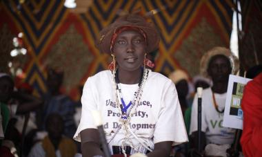"A South Sudanese woman at the Join Me on the Bridge event looks into the camera with a white shirt that seems to read, ""Unity, Peace, Prosperity, and Development"""
