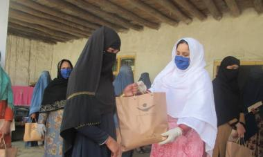 A woman in black receives a paper bag with the Women for Women International logo on it, a hygiene kit to help protect against disease, from a Women for Women International staff member