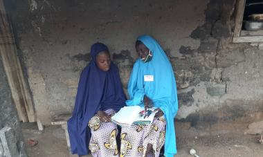 Aishatu sits with her daughter, Ummi, on a bench as they go through the Women for Women International handbook
