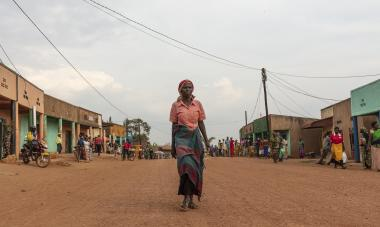 A woman stands tall in the middle of a road in Rwanda, centered in the frame; Photo Credit: GiveWith