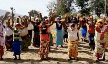 A group of women and their trainers in Jos Plateau State, Nigeria jumping and shouting with their hands in the air, though their faces are covered by masks, to express their gratitude