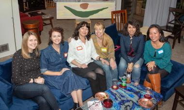 Photo of six women on a couch, smiling at the camera, with a poster of the Women for Women International logo behind them. Photo provided by Liliana Soroceanu