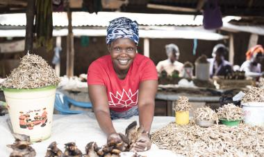 Alice smiles up at the camera from her stall, where she sells fish; Photo credit: Charles Atiki Lomodong