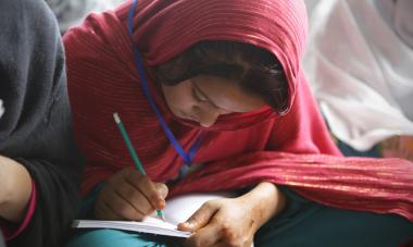 woman in a red headscarf writing