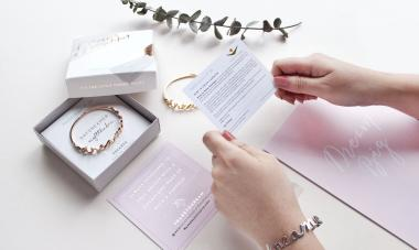 hands holding gift set with bracelet and card