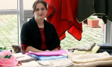 woman sitting behind table with piles of clothes