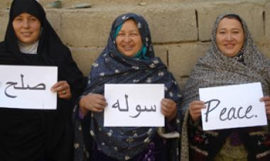 three women holding signs that say peace in different languages