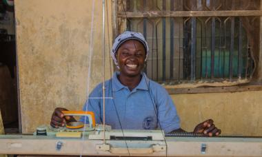 Nigeria - woman smiling at sewing machine