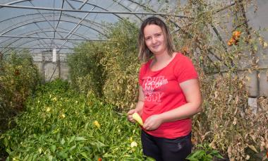 Bosnia - woman in greenhouse showing off veggies