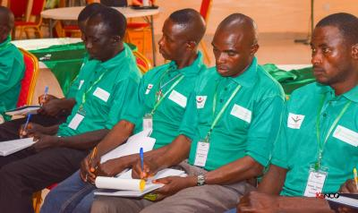 men in green shirts taking notes