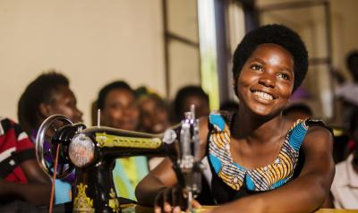 Rwanda - woman at sewing machine smiling